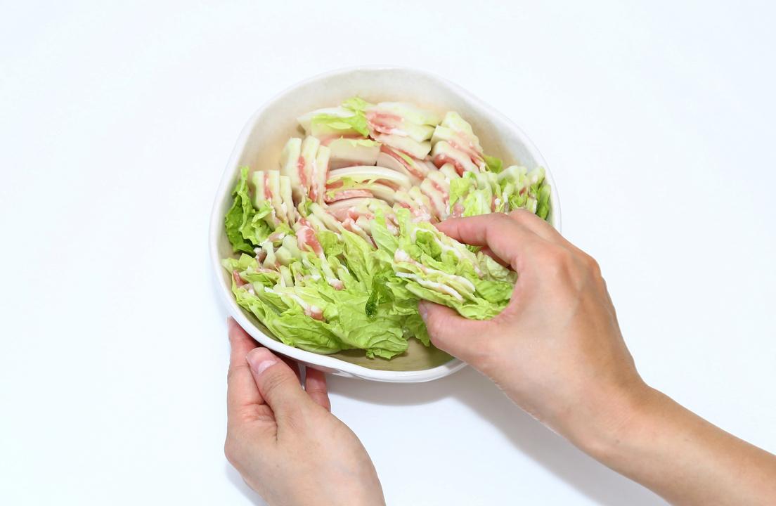 切った白菜と豚肉を耐熱皿に入れるところ