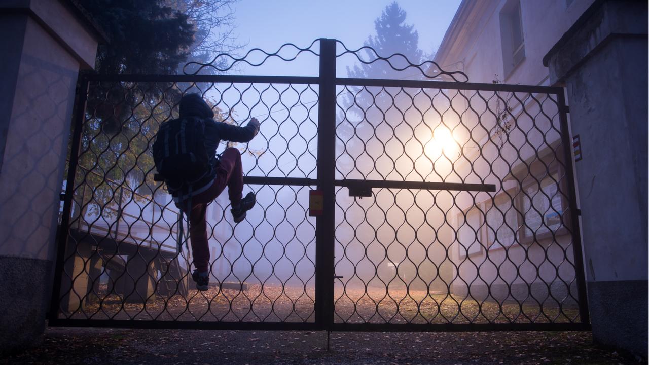 壁を乗り越えようとする男性