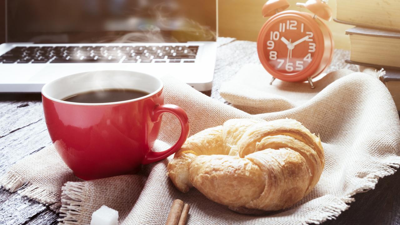 パソコンの前に置かれたコーヒーとパン