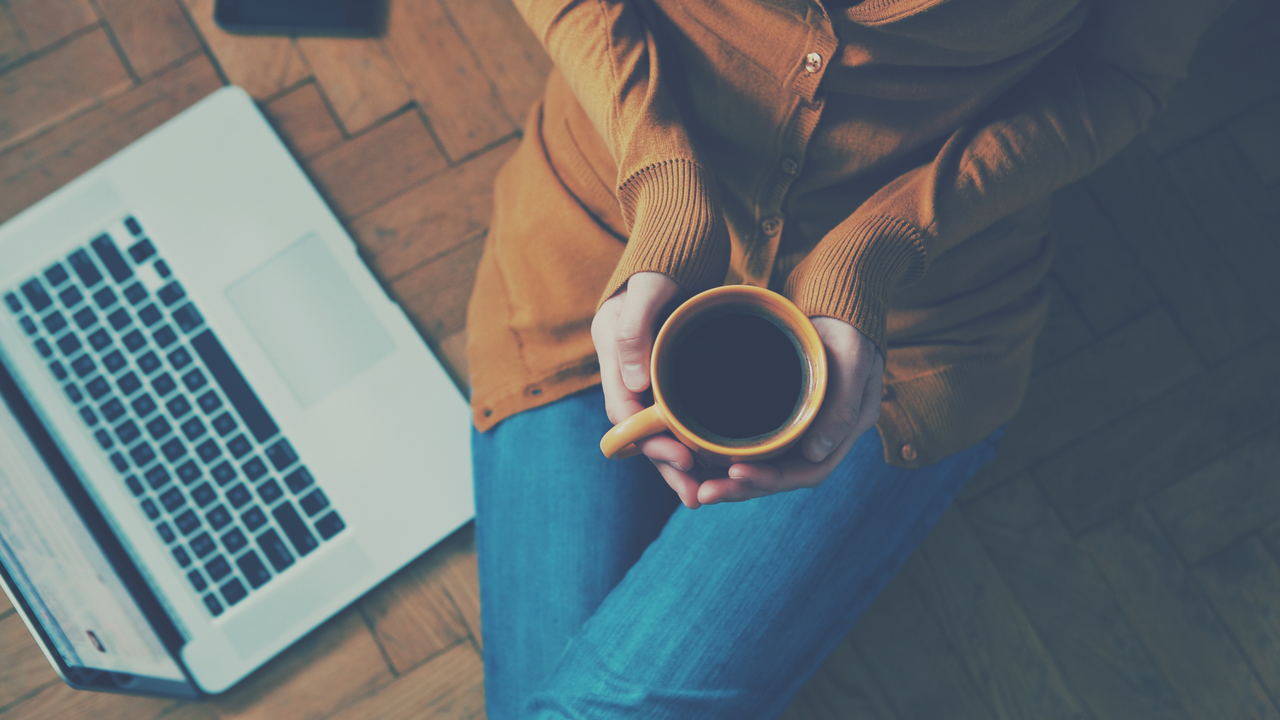 コーヒーを両手で持つ女性