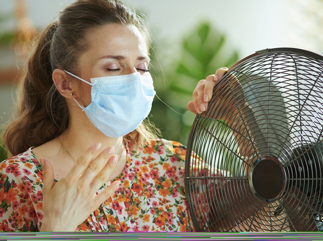 マスクをつけて暑がる女性