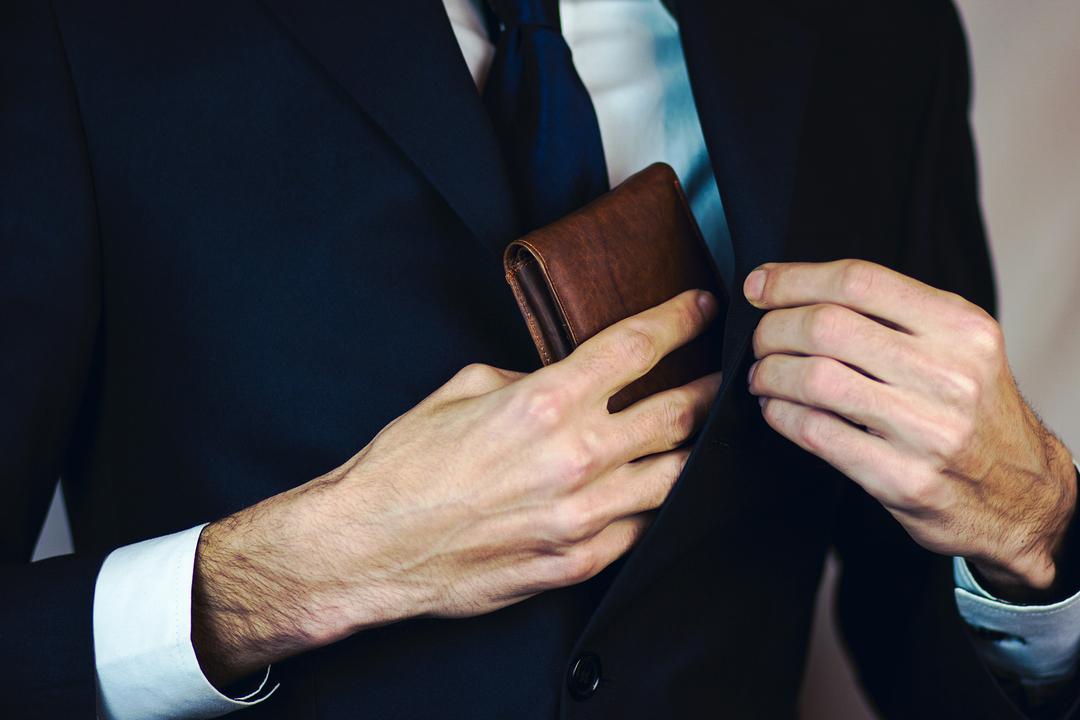 財布を胸ポケットに入れる男性