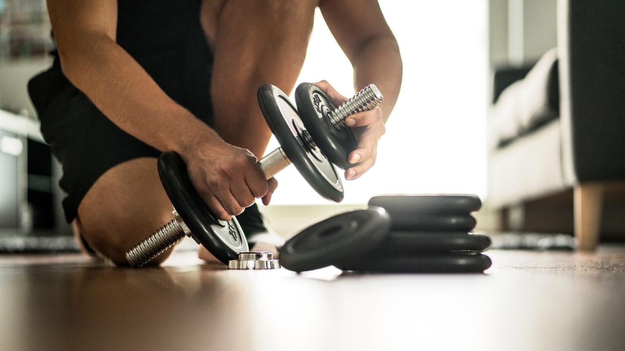 ダンベルの重さを調整する男性