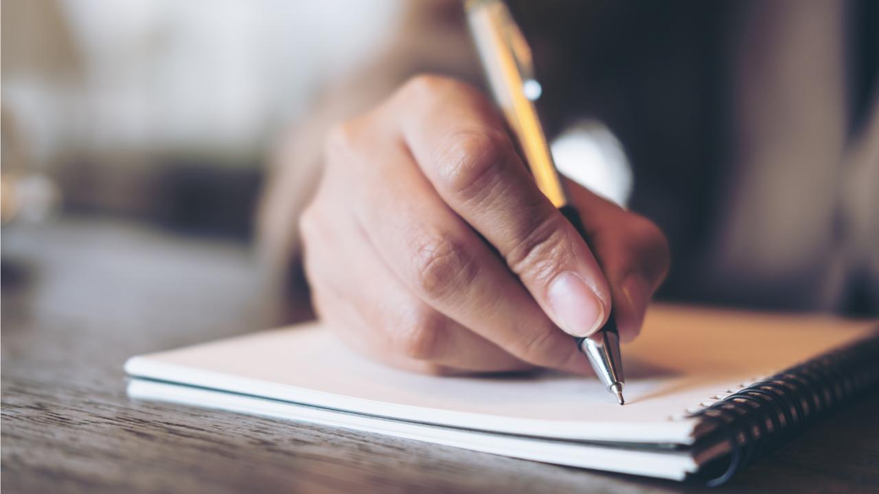 紙のノートにペンで文字を書き出す様子