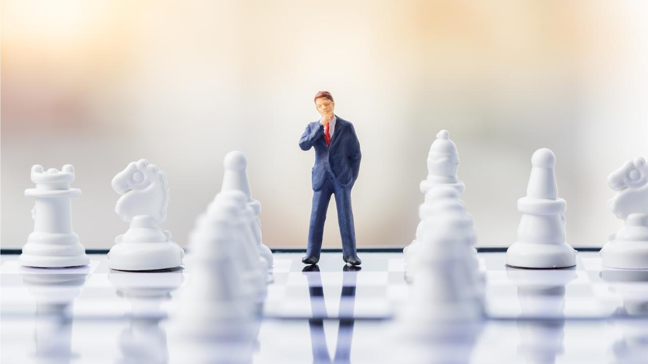 チェス盤の上で悩む男性のフィギュア