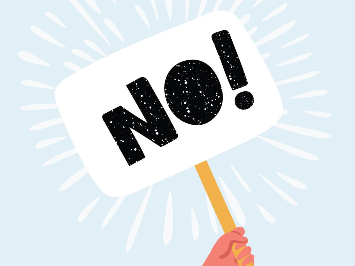 「NO!」と書かれたプラカードを掲げる様子