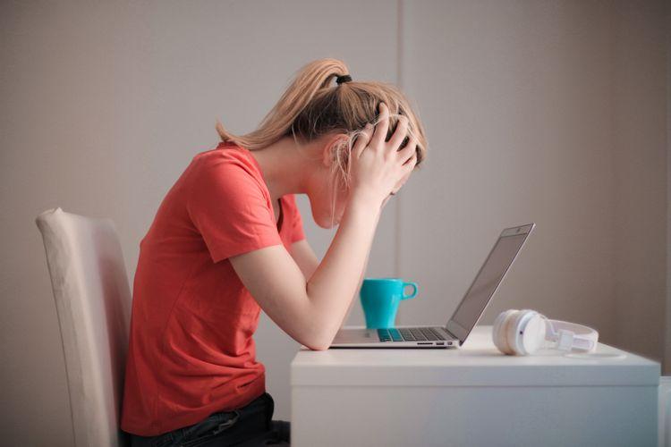 パソコンに向かって頭を抱える女性
