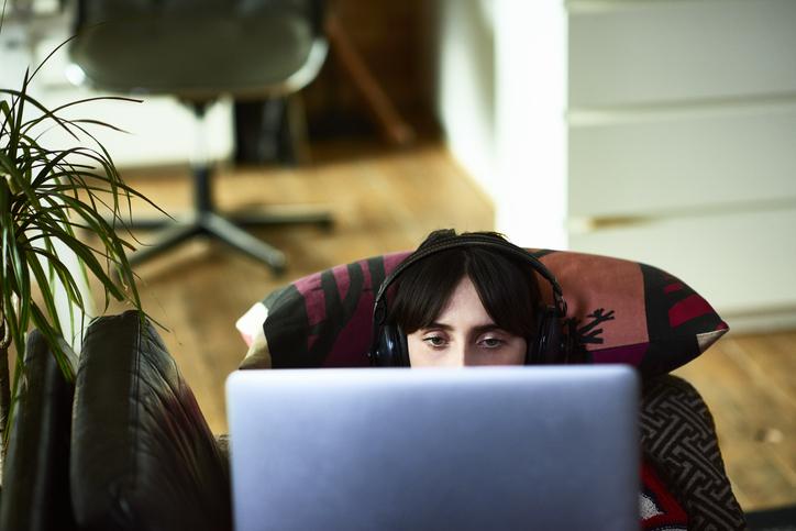 ヘッドホンをつけてパソコンを見る女性