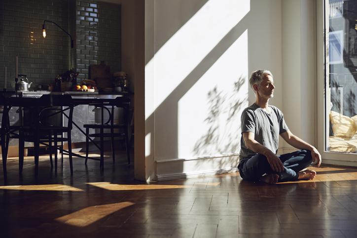 部屋で瞑想する男性