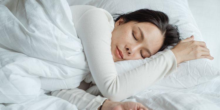 布団に入って眠る女性