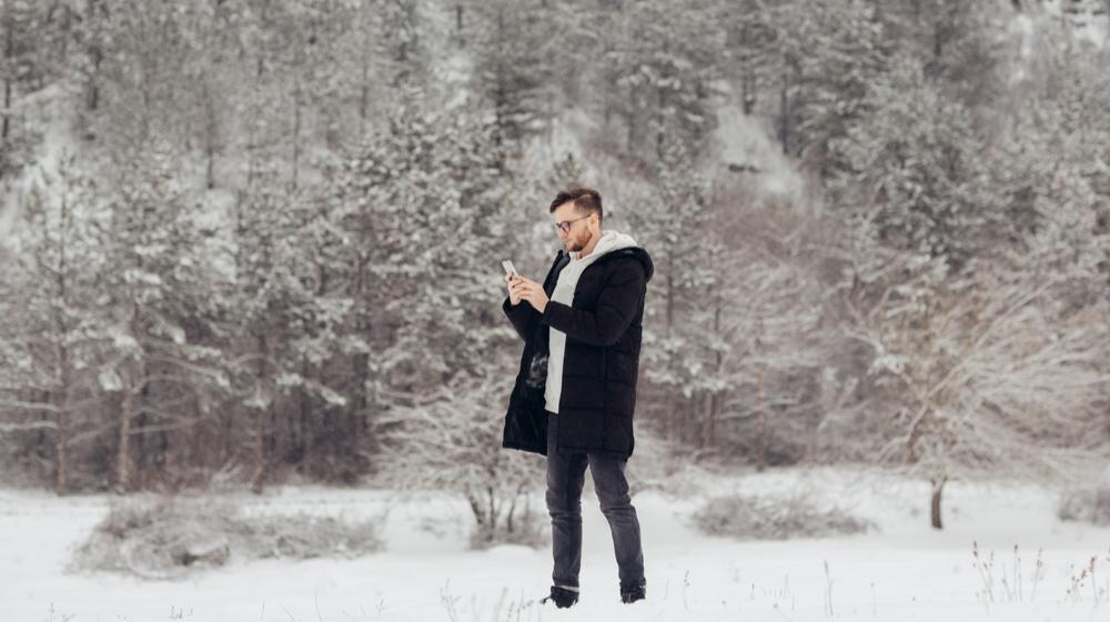 雪山でスマホを見る男性