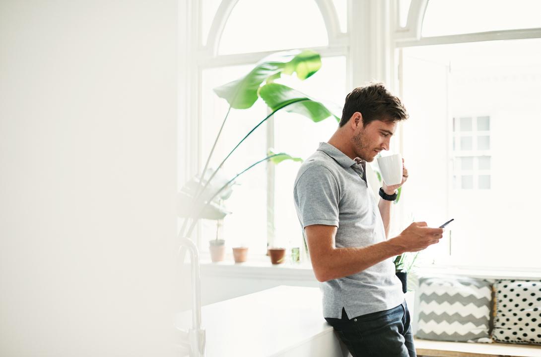 自宅でコーヒーを飲みながらスマホを操作する男性