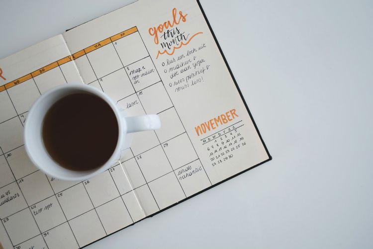 スケジュール帳の上にコーヒー