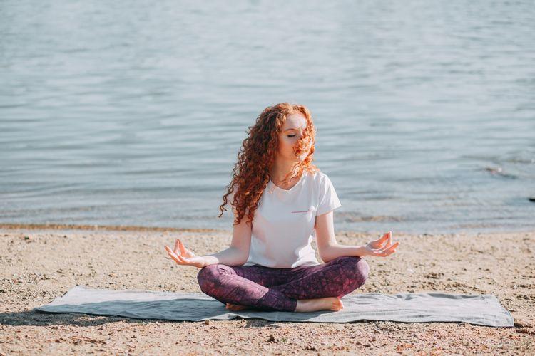 ビーチで瞑想する女性