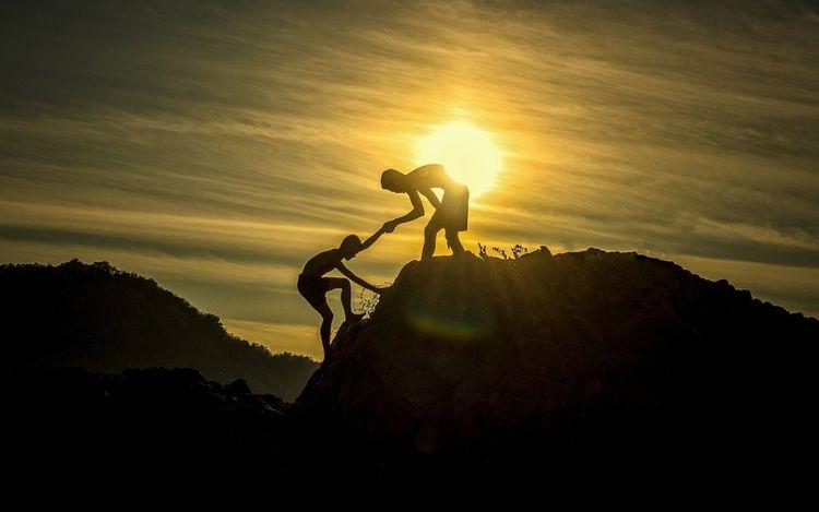 助け合って山を登るイメージ
