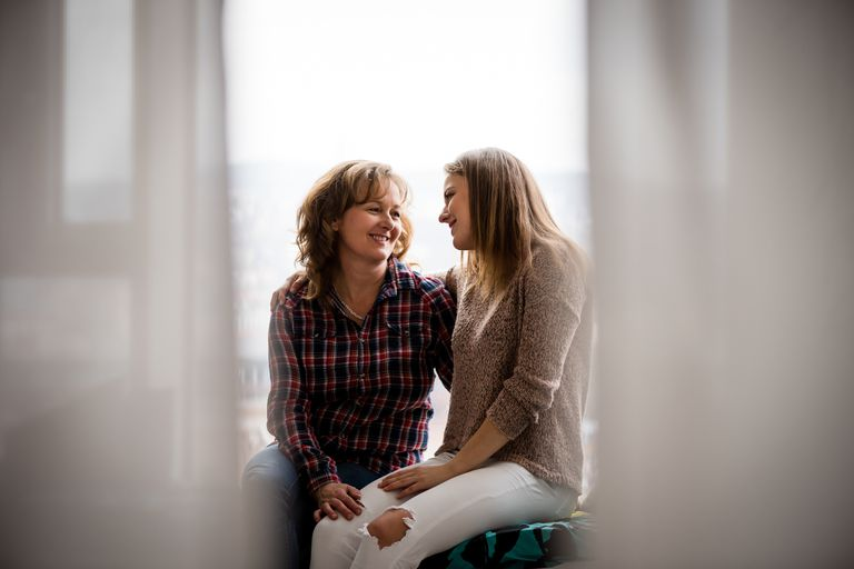 adult-daughter-and-mother-conversing-at-window-royalty-free-image-694727994-1535640624