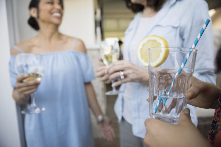 women-drinking-white-wine-and-lemon-water-on-patio-royalty-free-image-719871045-1534869427