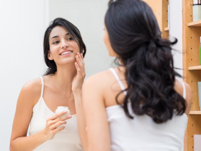 スキンケア中に、鏡を見て微笑む女性