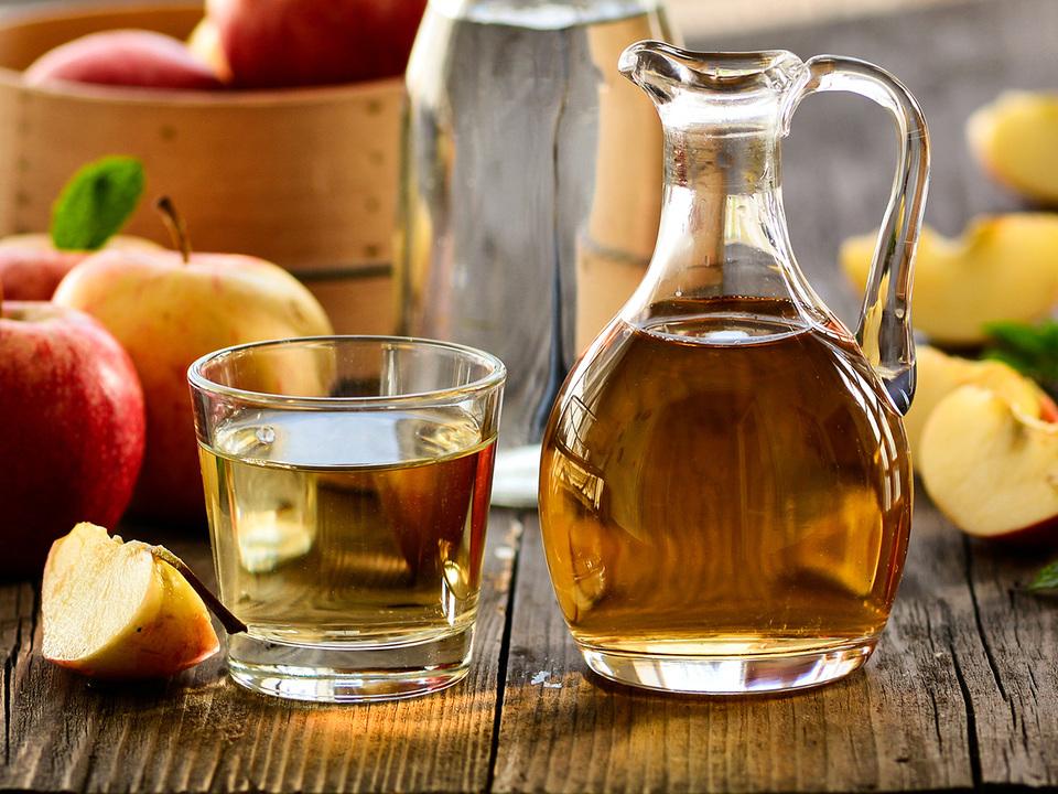 グラスとデカンタに入ったアップルビネガーとりんご