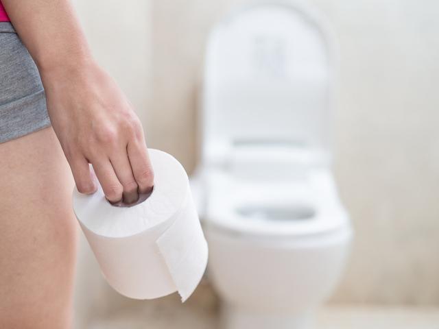 トイレットペーパーを持つ女性