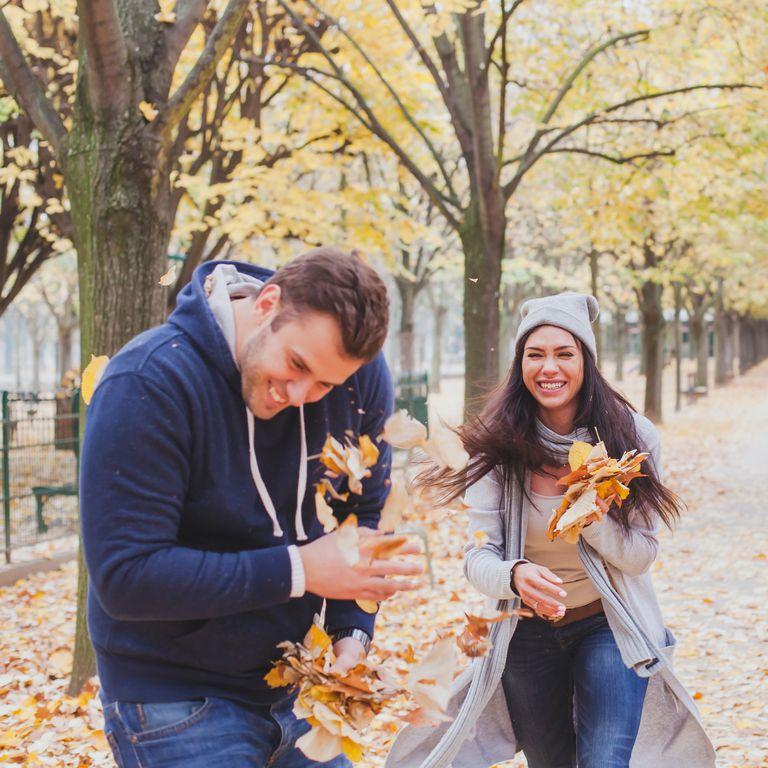 落ち葉で遊ぶ男女