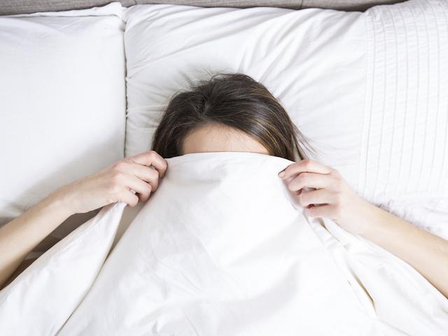 顔までふとんをかぶって寝ている女性