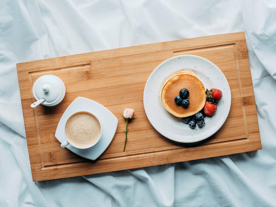 木製トレーにのったパンケーキとコーヒー