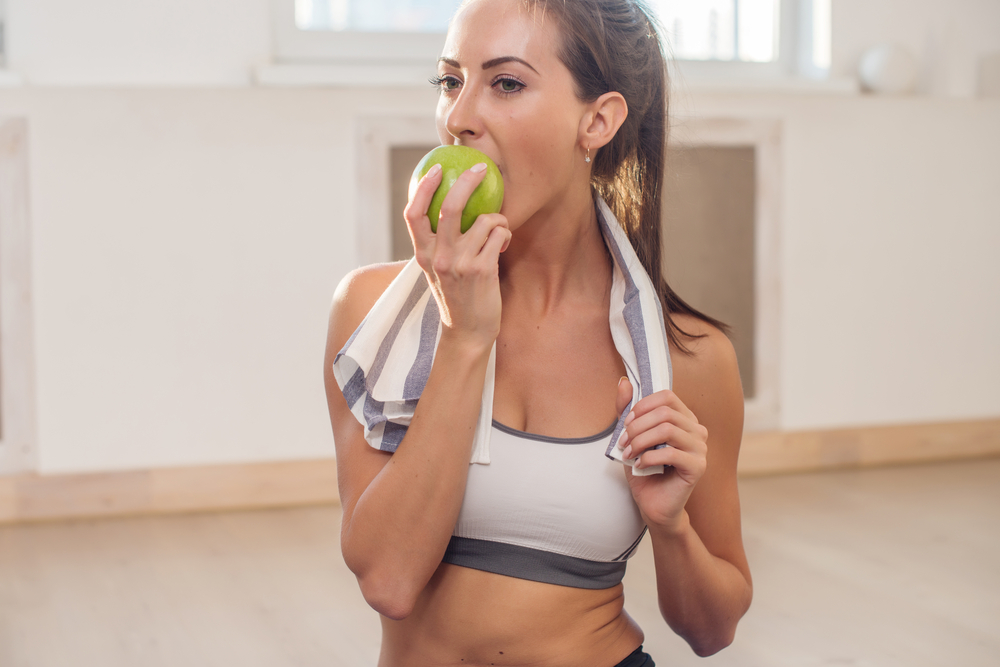 りんごをかじる運動後の女性