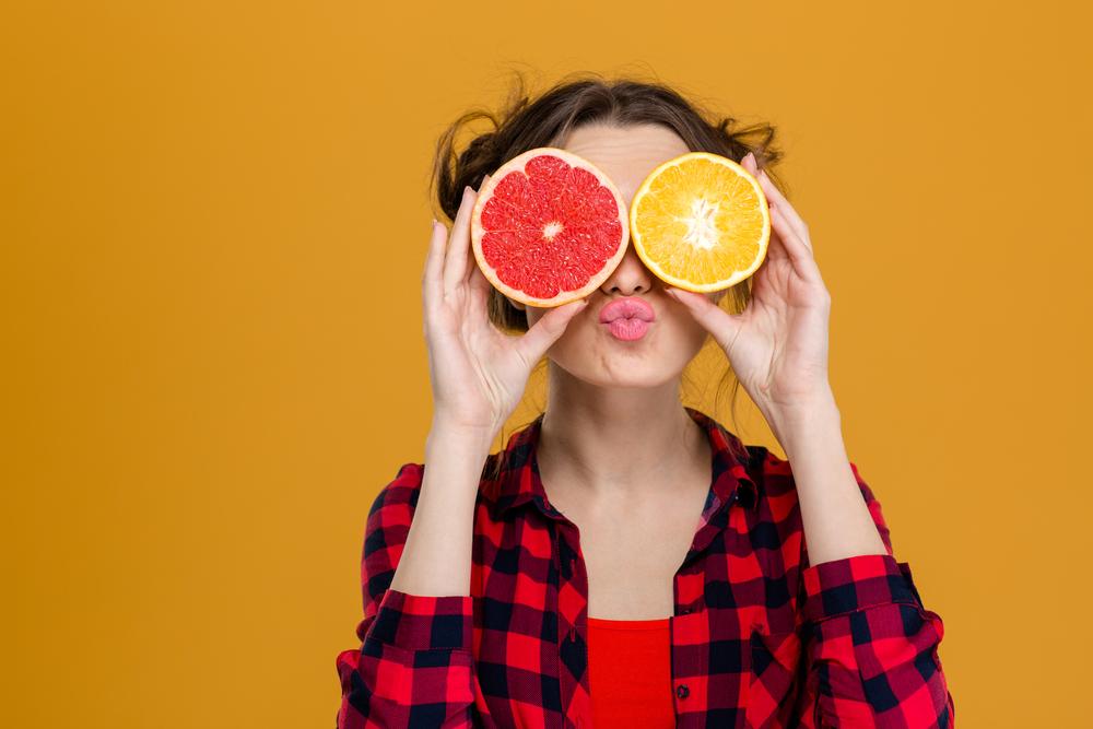グレープフルーツで顔を隠した女性