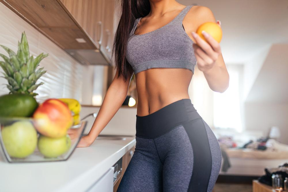 トレーニングウェアで果物を手に取る女性