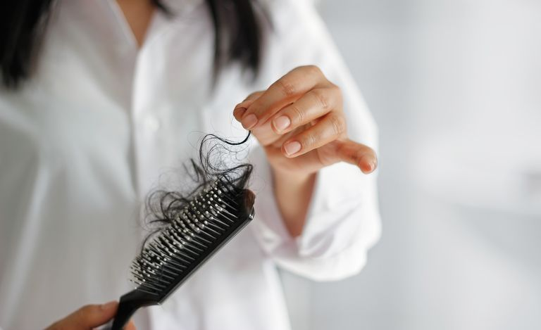 woman-losing-hair-on-hairbrush-in-hand-on-bathroom-royalty-free-image-846216978-1539032249