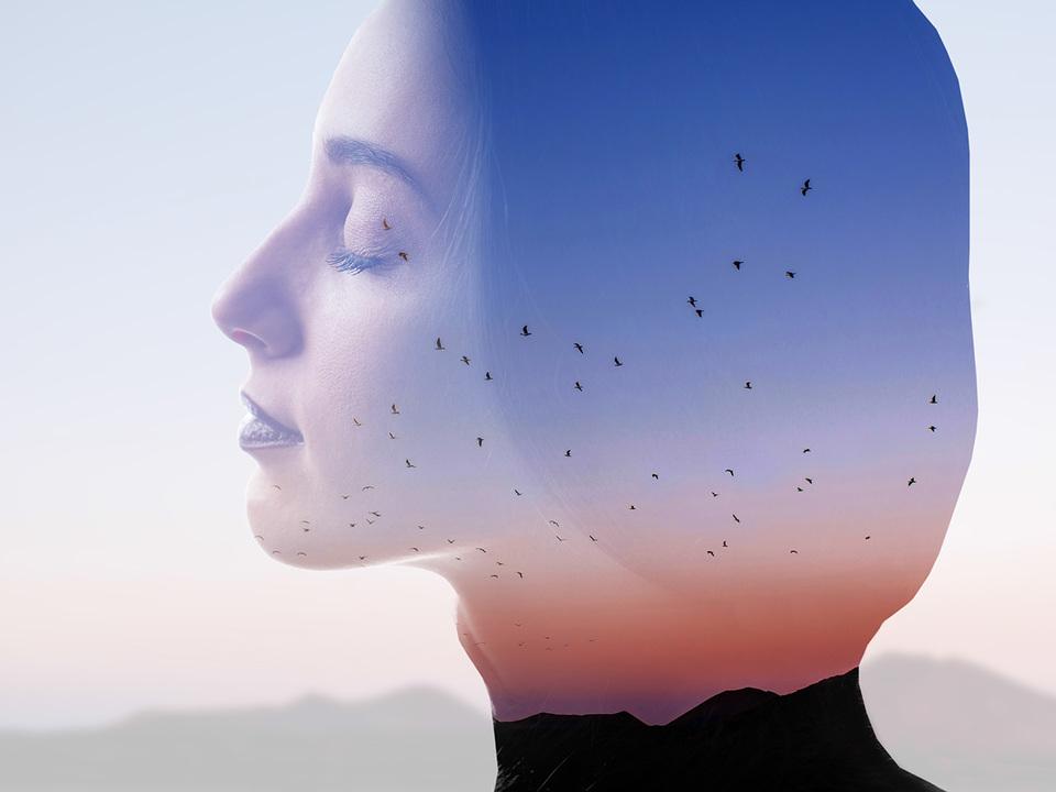 山と鳥と女性のシルエットと、日没の空と二重露光写真