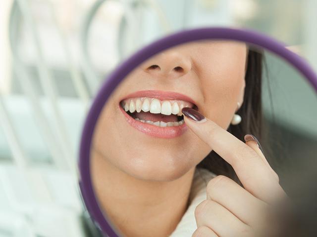鏡で口もとを確認する女性