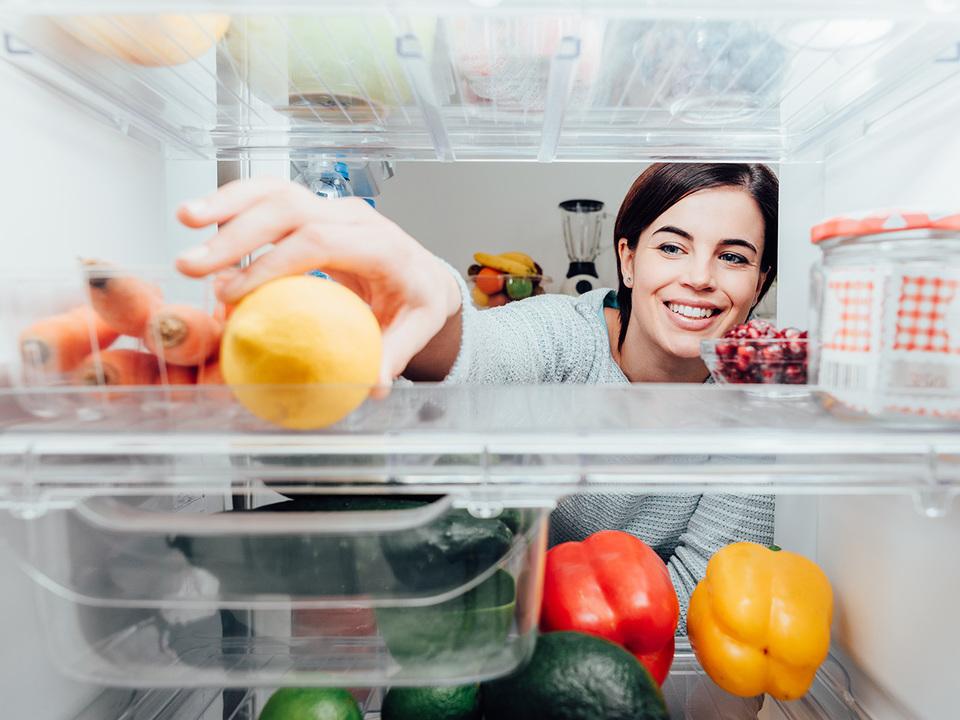 冷蔵庫からレモンを出す女性