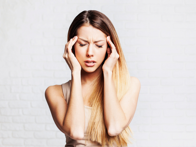 頭を抑える女性
