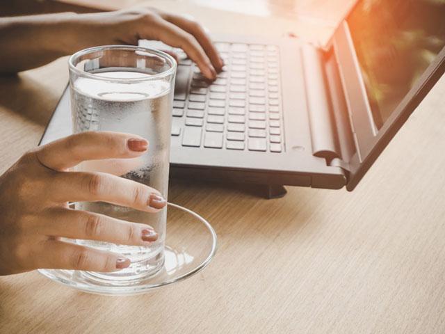 パソコンをしながら水を飲む女性