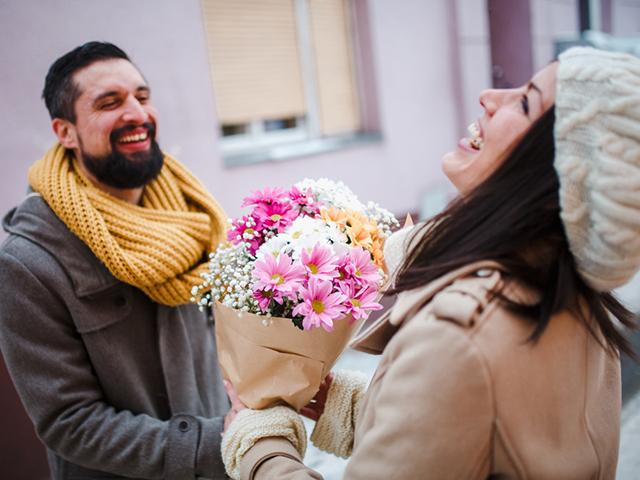 男性から花束を贈られる女性