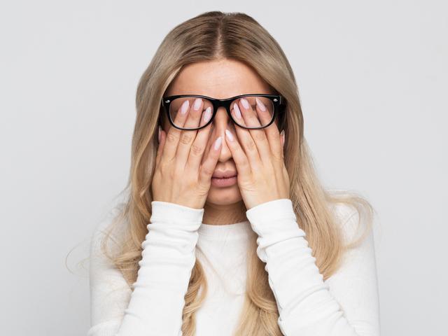目を抑える女性