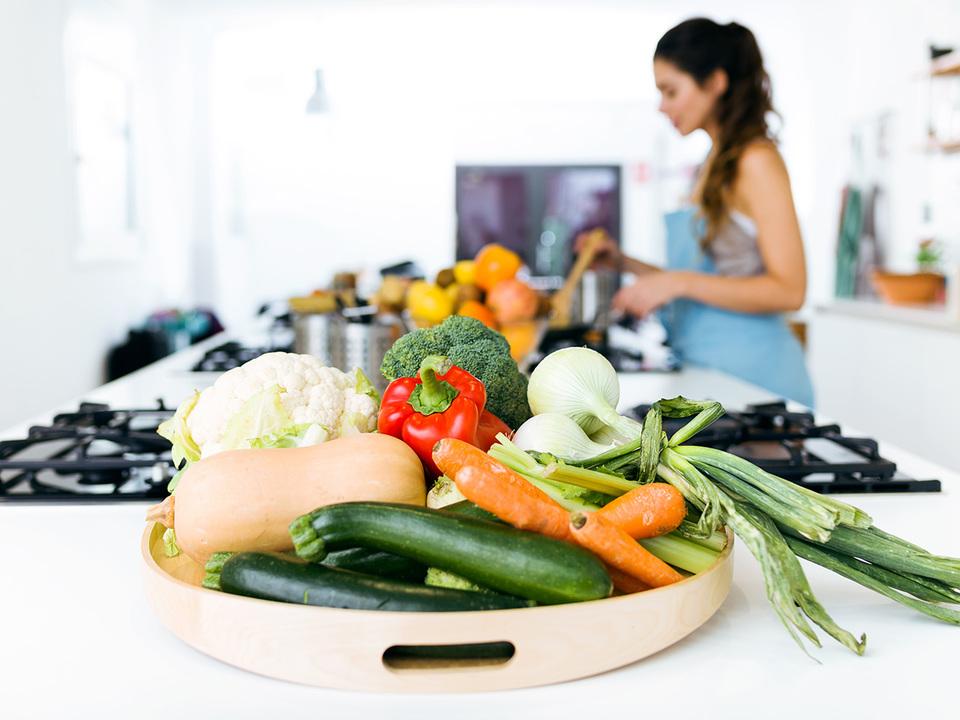 キッチンで料理をする女性と野菜