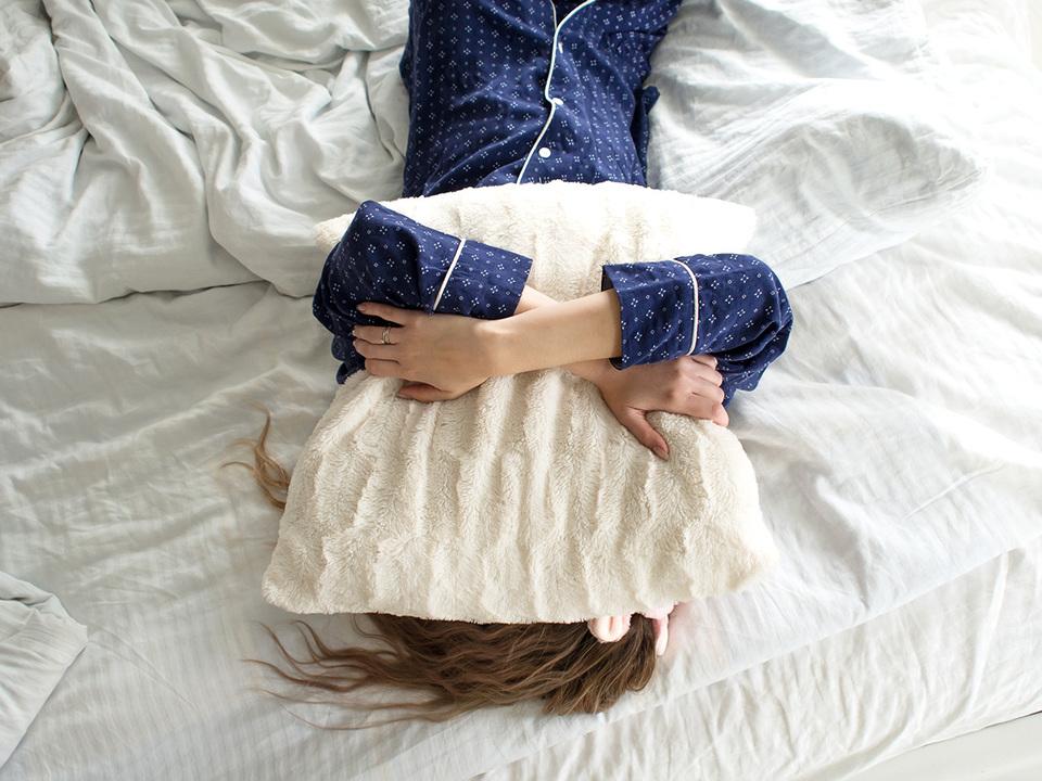 タオルを抱いて寝る女性