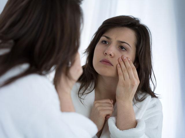 鏡を見てシワを気にしている女性
