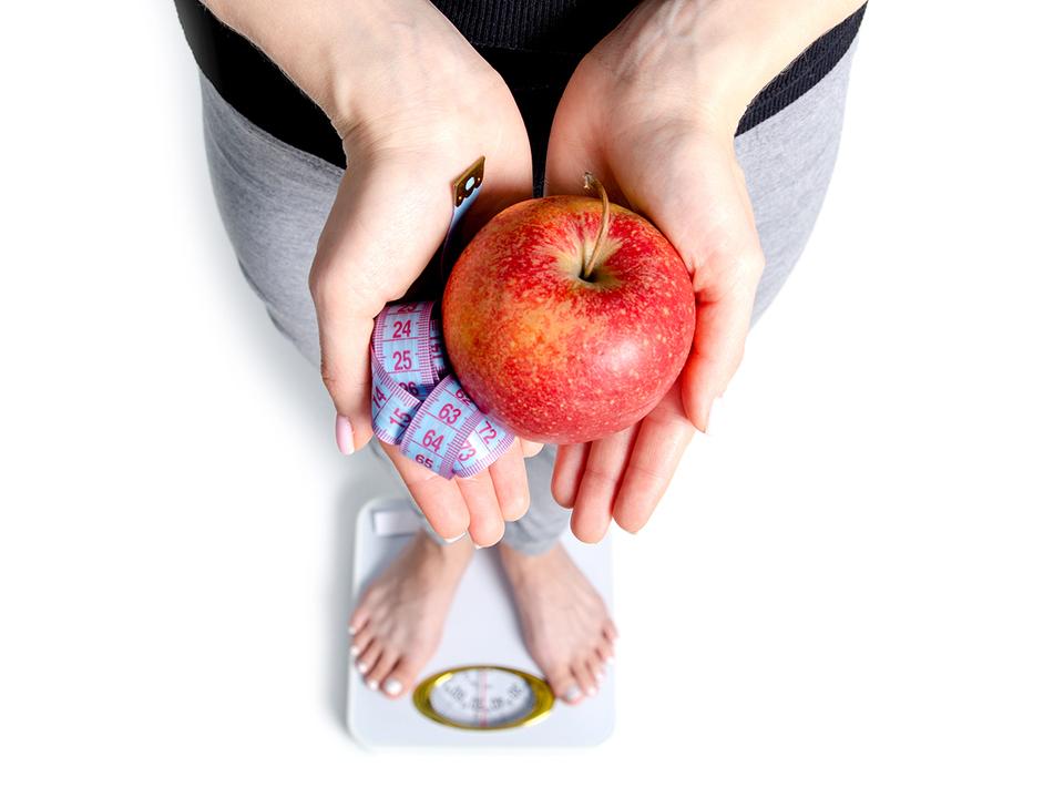 体重計にのるダイエット中の女性