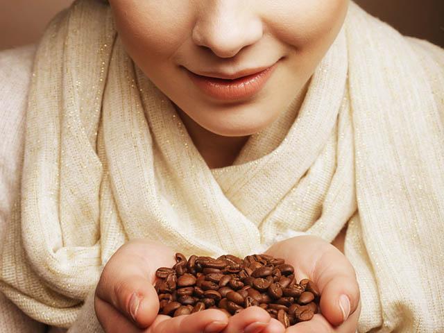コーヒー豆の匂いを嗅ぐ女性