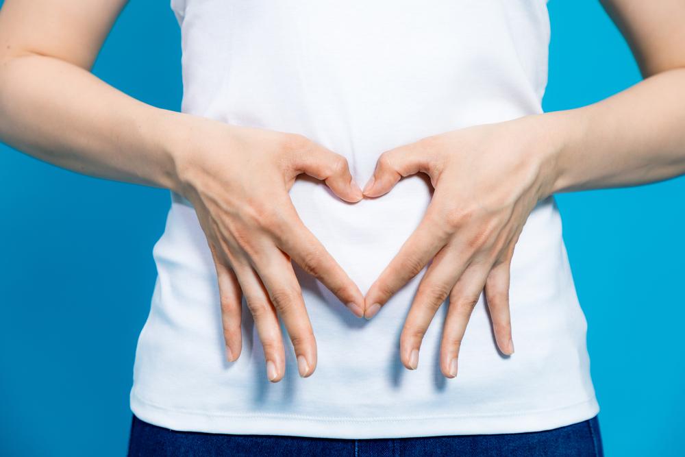 腸を指す女性