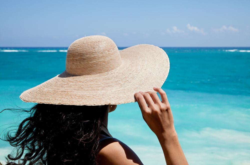 帽子で日除けする女性