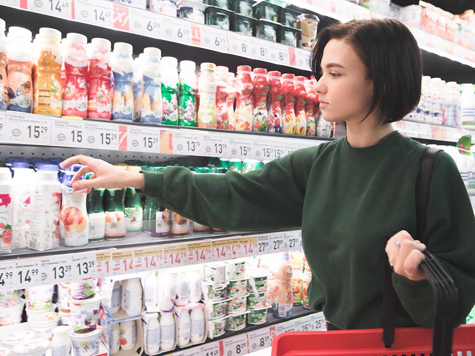 スーパーで飲むヨーグルトを選ぶ女性