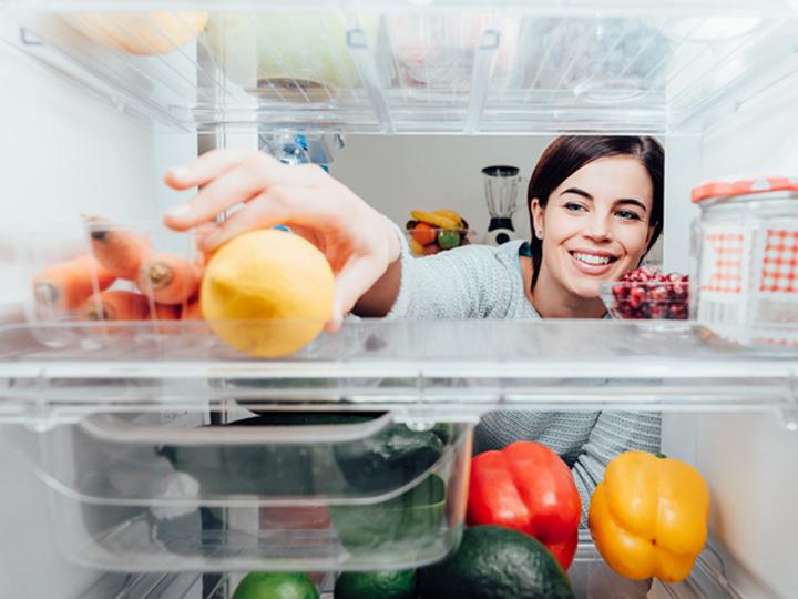 冷蔵庫から食べ物を取る女性