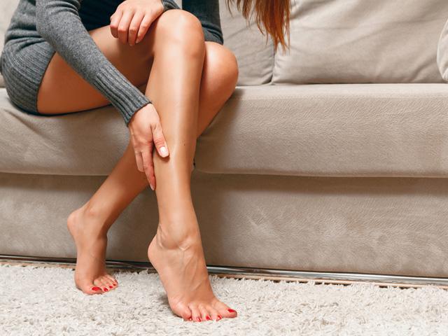 足に触れる女性
