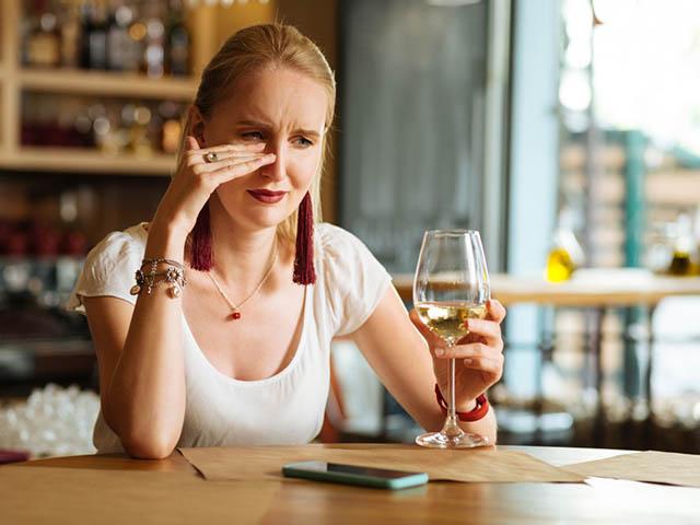 泣きながらお酒を飲む女性