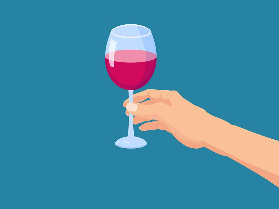 赤ワインが入ったグラスを持つ人